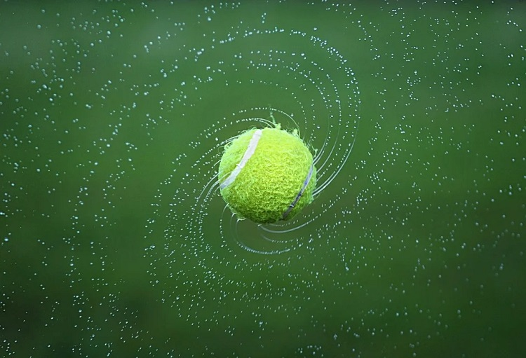 A tennis ball and water droplets