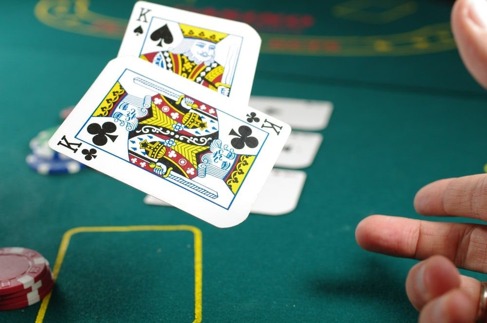 a hand throws a pair of Kings onto a felt gaming table