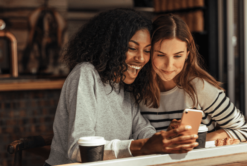 women using online dating app on phone together