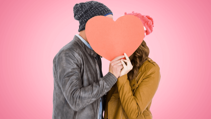 couple hiding faces behind paper heart