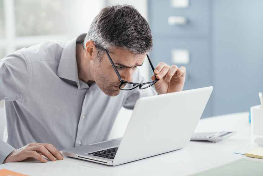 man with glasses looking closely at computer