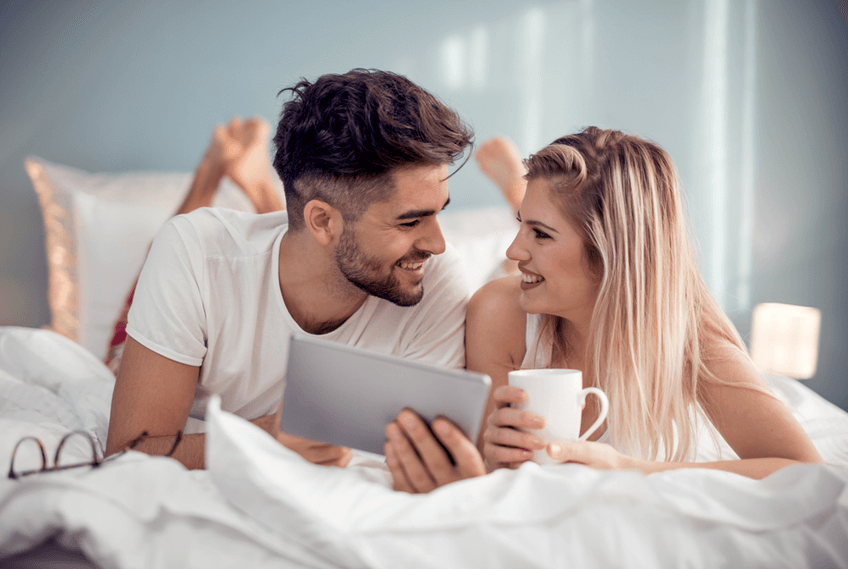couple drinking coffee in bed