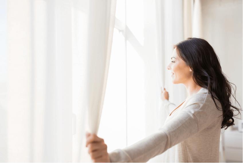 woman closing curtains